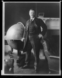 Theodore Roosevelt, full-length portrait, standing beside large globe.