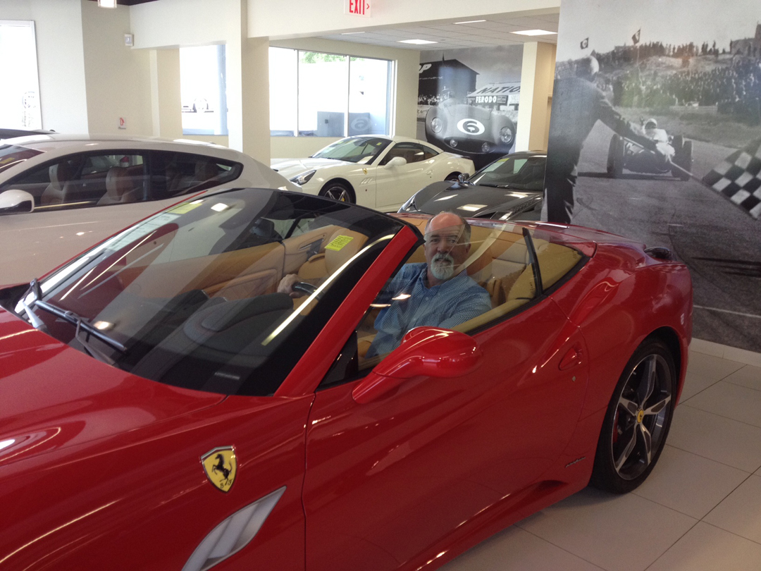 Bruce sitting in a Ferrari putting a real car to his goals